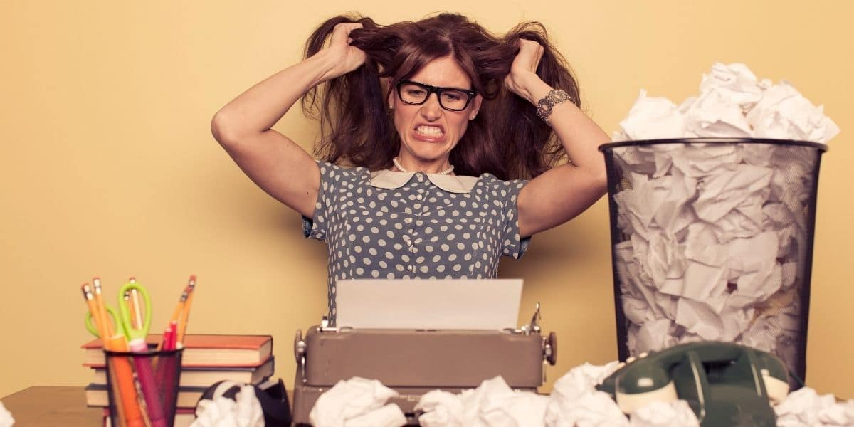 writer pulling her hair surrounded by crumpled papers