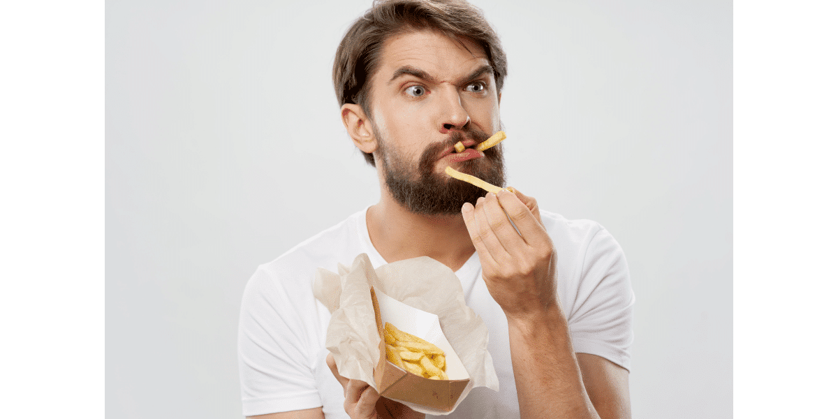 Man eating french fries with a curios look on his face