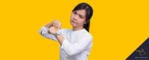 Woman pointing at watch with questioning look on her face