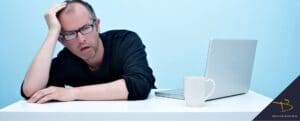 Man looking very bored next to laptop and coffee mug